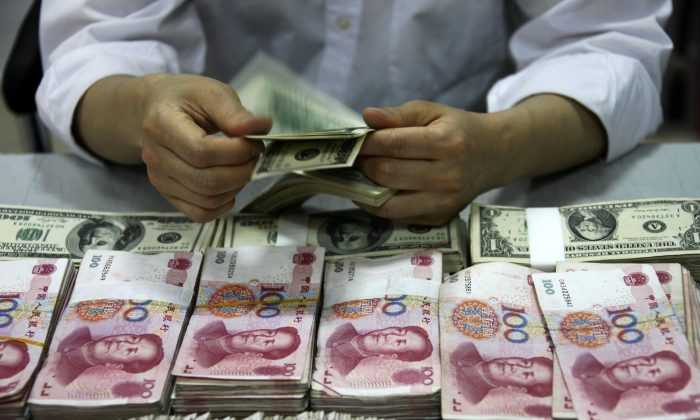 U.S. dollar notes are counted next to stacks of Chinese 100 yuan bank notes at a bank in Huaibei, Anhui Province, China. (STR/AFP/Getty Images)