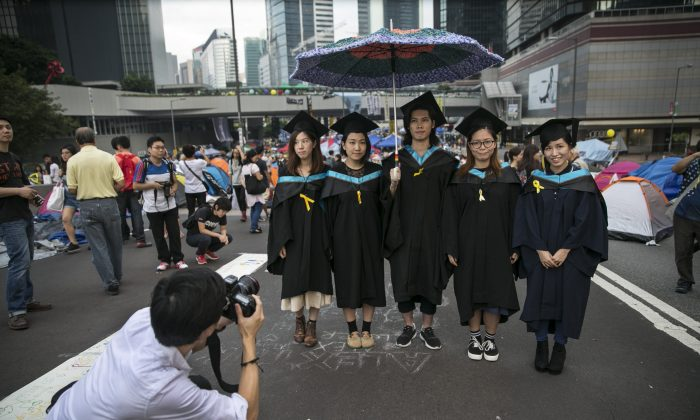 Graduates from the Hong Kong Polytechnic University pose for souvenir photos after their graduation ceremony at a main protest site of the Umbrella Movement on as a festival atmosphere prevails Oct. 26, 2014 in Hong Kong. In the aftermath of the pro-democracy protests, Hong Kong university students have shown a suspicion of communist influence on their campuses. (Paula Bronstein/Getty Images)