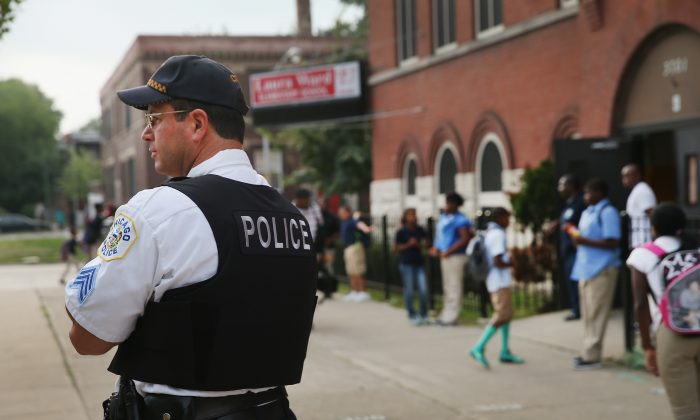 Chicago Police Sgt. Alan Lasch watches as students arrive at Laura Ward Elementary School on the Westside on August 28, 2013 in Chicago, Illinois. (Scott Olson/Getty Images)