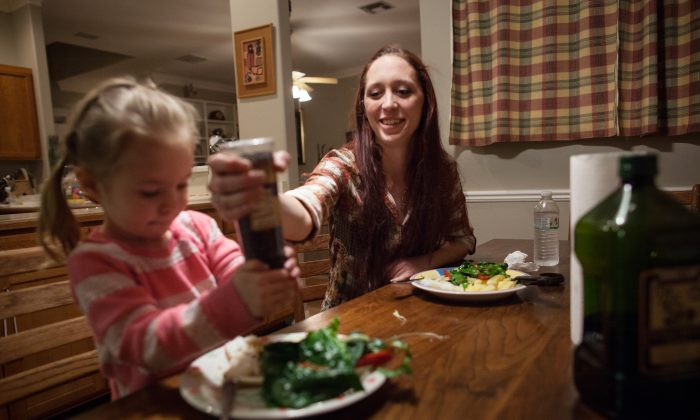 Maggie Barcellano, receiver of food stamps benefits, helps her daughter, Zoe, 3, use a pepper grinder with dinner at Barcellano's father's house in Austin, Texas on Saturday, Jan. 25, 2014. (AP Photo/Tamir Kalifa)