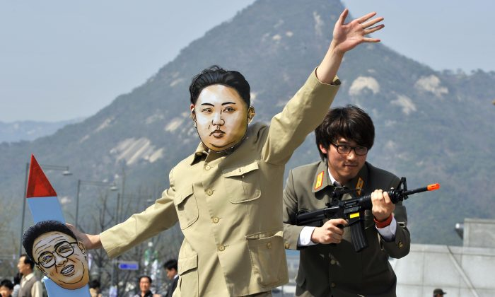 A South Korean activist (C) wearing a mask of North Korean leader Kim Jong-Un holds a mock missile during a rally denouncing North Korea's rocket launch and the three-generational dictatorship, in Seoul on April 15, 2012. (JUNG YEON-JE/AFP/Getty Images)