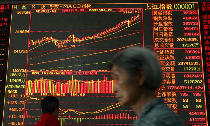 An investor walks past stock index a securities company in Wuhan, China, in this file photo. (China's stock rally will likely see intense turbulence in the near future. China Photos/Getty Images)