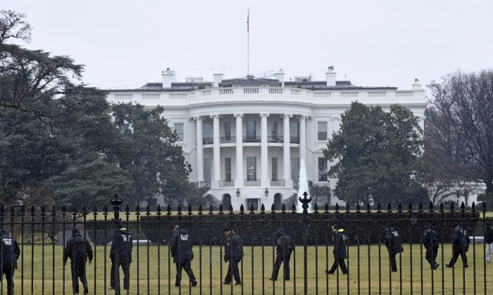 In this Jan. 26, 2015 file photo, Secret Service officers search the south grounds of the White House in Washington after an unmanned aerial drone was found on the White House grounds during the middle of the night. (AP Photo/Susan Walsh)