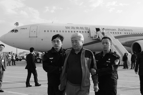 An Huimin (C) is brought back to China by a security detail on March 28, 2015. (Screen shot/ccdi.gov.cn)