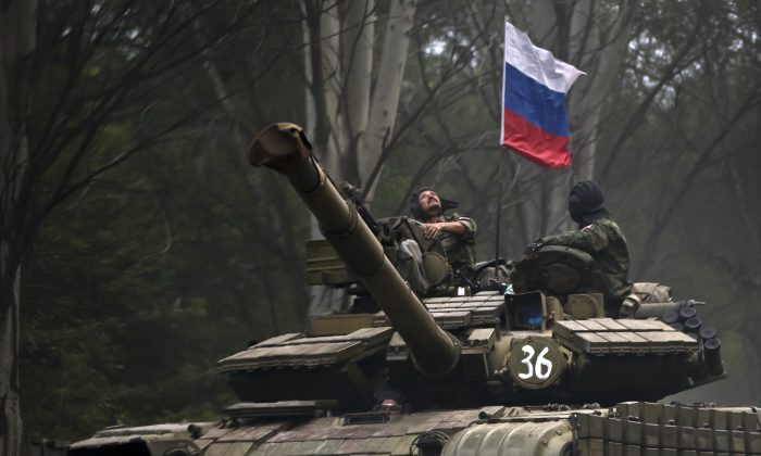 a pro-Russian rebel looks up while riding on a tank flying Russia's flag, on a road east of Donetsk, eastern Ukraine on July 29, 2015. (AP Photo/Vadim Ghirda)