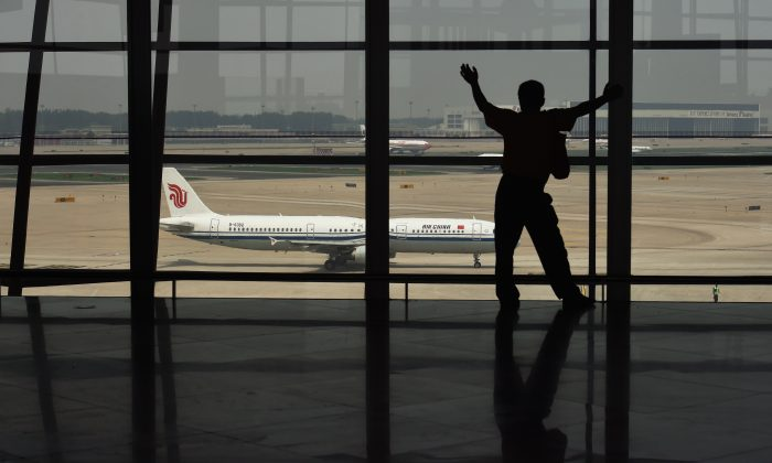 A man looks out at a plane through a window at Beijing international airport. (Greg Baker/AFP/Getty Images)