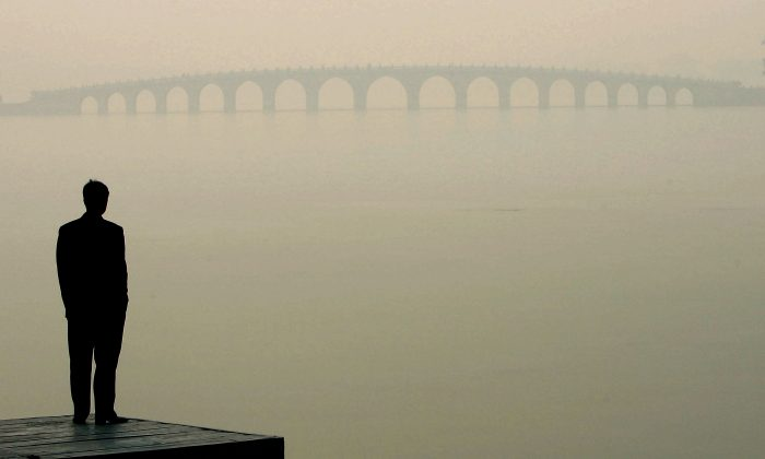 A man looks towards a bridge in heavy fog in Beijing in this file photo. (Guang Niu/Getty Images)