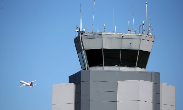 A plane takes off past the control tower at San Francisco International Airport on February 25, 2013 in San Francisco, California. Computers of the Federal Aviation Administration were recently attacked by hackers. (Justin Sullivan/Getty Images)