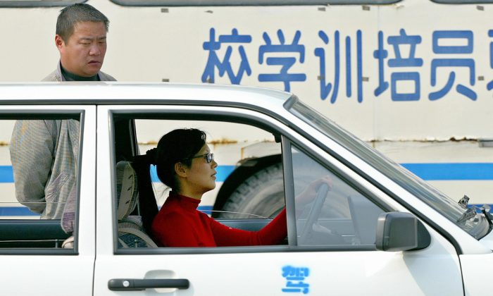 "A female trainee (R) studies driving as a teacher watches her at a driving school in Shanghai, 06 April 2004. Bribing driving examiners has become an ""unspoken rule"" in China to pass the driving tests and get a driver's license. (Liu Jin/AFP/Getty Images)"