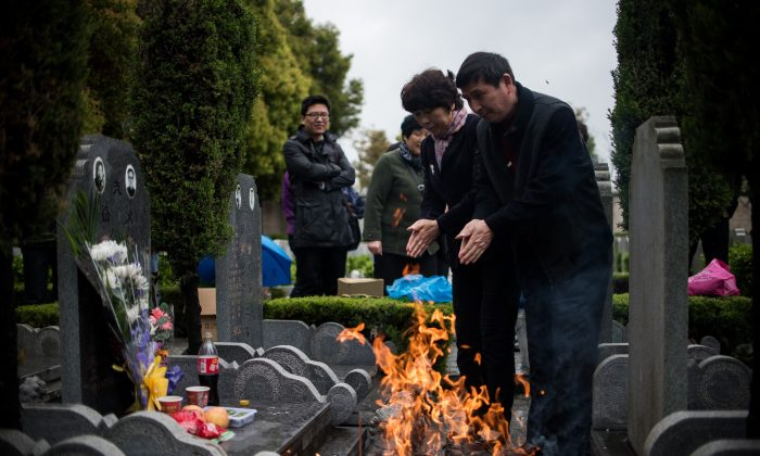 Photo Caption: A couple prays as they burn paper money during the annual 'Qingming' festival, or Tomb Sweeping Day, at a public cemetery in Shanghai on April 6, 2015. (Johannes Eisele/AFP/Getty Images)