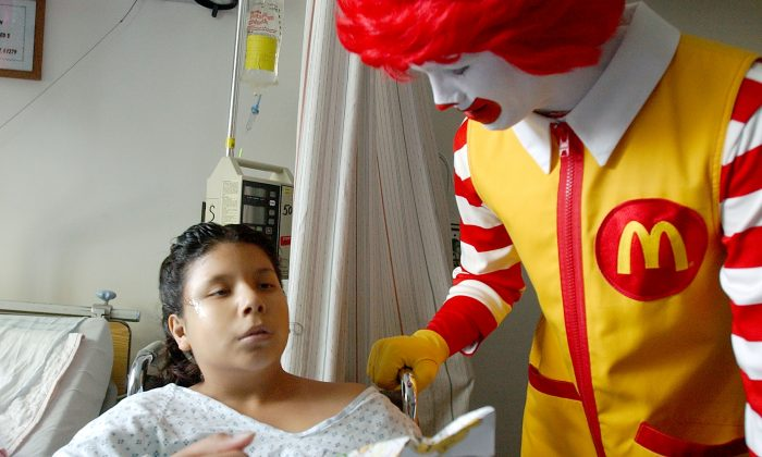 Ronald McDonald  meets with a 9-year-old girl at the San Jose Medical center in California in this file photo. (Justin Sullivan/Getty Images)  9-year-old Amanda Cardenez December 18, 2001 at a visit to San Jose Medical center in San Jose, CA. McDonald flew in a CalStar medical helicopter to Bay Area hospitals to bring gifts to children. (Photo By Justin Sullivan/Getty Images)