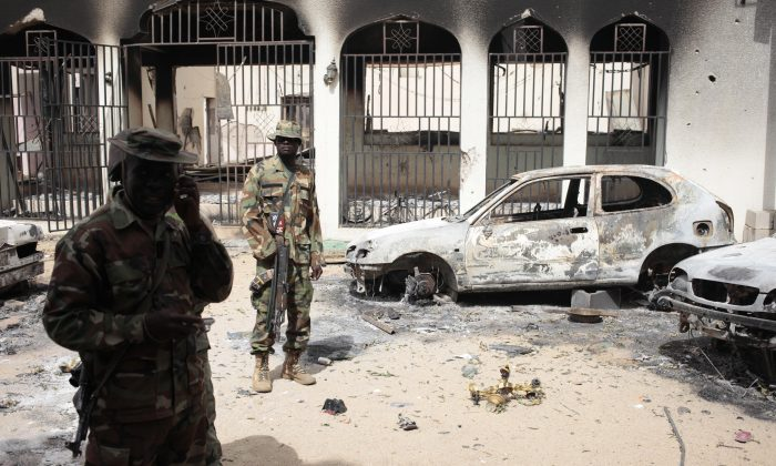 Nigerian soldiers stand guard in front of the burned out palace of the Emir of Gwoza, in Gwoza, Nigeria (AP/Lekan Oyekanmi)