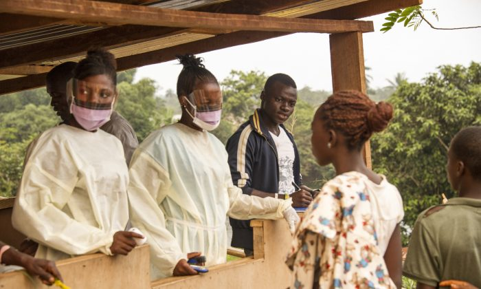 Sierra Leone health officials check passengers transiting at the border crossing with Liberia in Jendema on March 28, 2015. The authorities in Sierra Leone started enforcing on March 27 a three-day lockdown to curb the spread of Ebola, with the entire population ordered to stay at home. (Zoom Dosso/AFP/Getty Images)