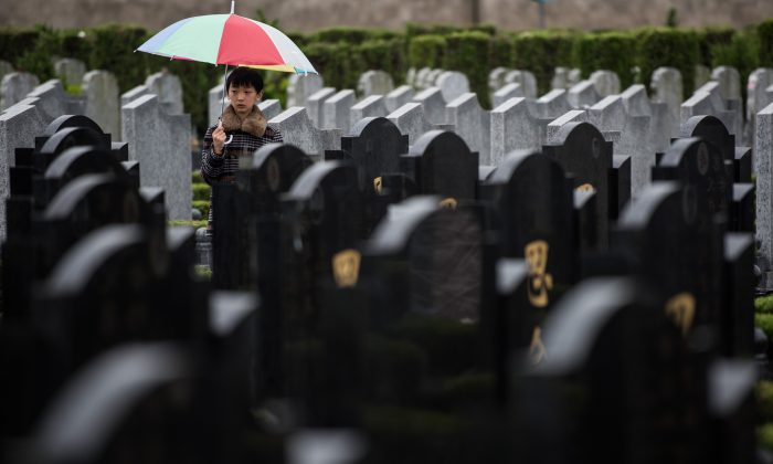 """A boy stands between graves during the annual """"Qingming"""" festival, or Tomb Sweeping Day, at a public cemetery in Shanghai on April 6, 2015. (Johannes Eisele/AFP/Getty Images)"""