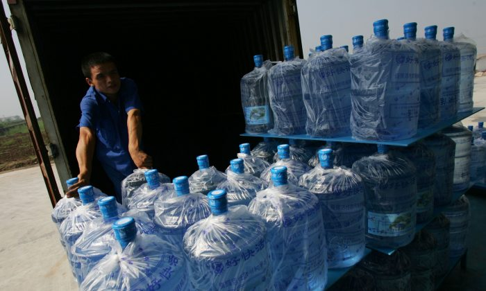 A worker loads bottled drinking water onto a van at a bottling factory July 22, 2007 in Xian of Shaanxi Province, China. One sixth of the 650,000 filtered water bottles sold in Beijing daily contain water from the tap, according to Beijing Association for Barreled Drinking Water. (China Photos/Getty Images)