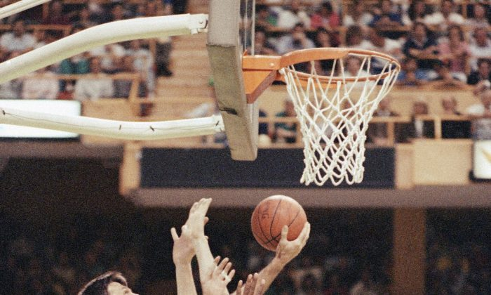 Boston Celtics forward Kevin McHale (L) puts the ball through the out-stretched arms of Indiana Pacers forward Chuck Person (R) and center Rik Smits for the basket during first period action of their NBA playoff contest, Friday night, April 26, 1991 at the Boston Garden in Boston. (AP Photo/Eric Risberg)