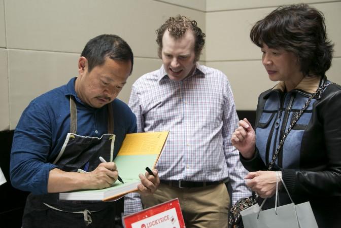 Pichet Ong signs cookbooks. (Samira Bouaou/Epoch Times)