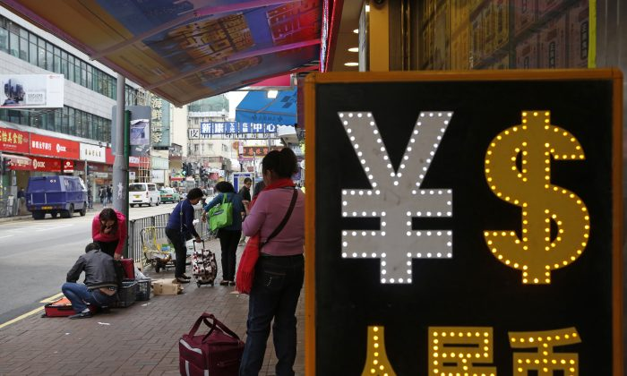 A trader packs goods near a currency exchange shop in Hong Kong, on April 10, 2015. (AP Photo/Kin Cheung)