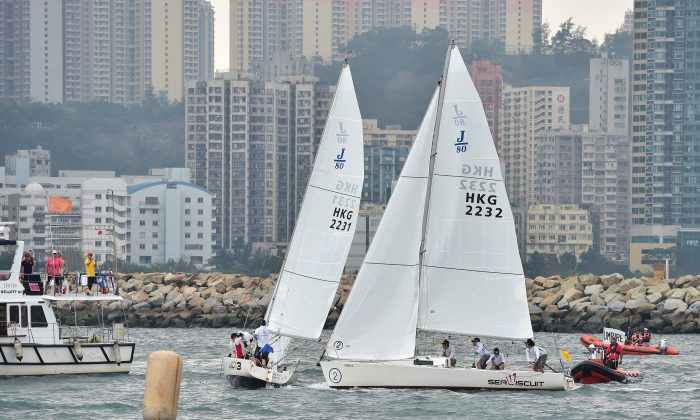 Regatta winner Maximilian Soh (Sail 2232) of Singapore, 'fights' with runner up Jeremy Koo (2231) of Malaysia before the start of their round robin match in the Hong Kong International Match Racing Regatta, organized by the Royal Hong Kong Yacht Club and held in Victoria Harbour on Saturday and Sunday April 18-19, 2015. (Bill Cox/Epoch Times)