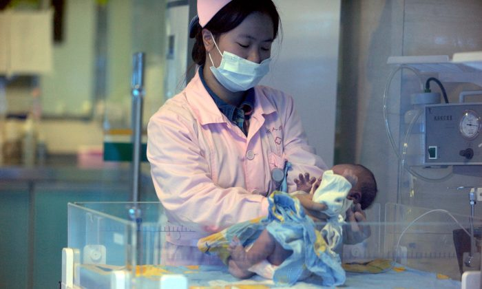 A nurse looks after a rescued baby in a hospital in Xichang, southwest China's Sichuan province, on Dec. 18, 2012. A baby smuggling ring was recently broken up in China. (STR/AFP/Getty Images)