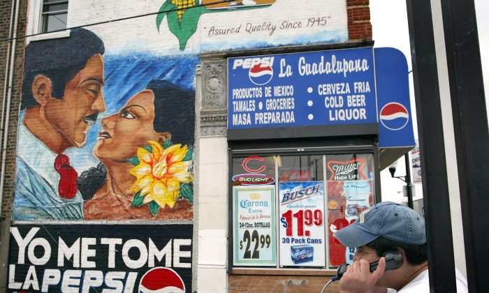 A Hispanic man talks on a public phone near a Pepsi wall ad in Spanish in Chicago's mainly Hispanic Little Village neighborhood on Sept. 22, 2003. (Tim Boyle/Getty Images)