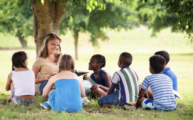 A young woman at work as educator reading book to boys and girls in the park via Shutterstock*