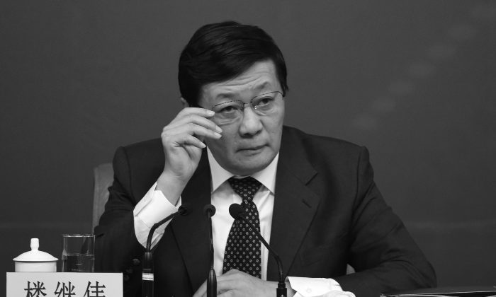 """Chinese Finance Minister Lou Jiwei attends a press conference in Beijing on March 5, 2015. Lou warned that China could be headed toward """"middle-income trap."""" (Wang Zhao/AFP/Getty Images)"""