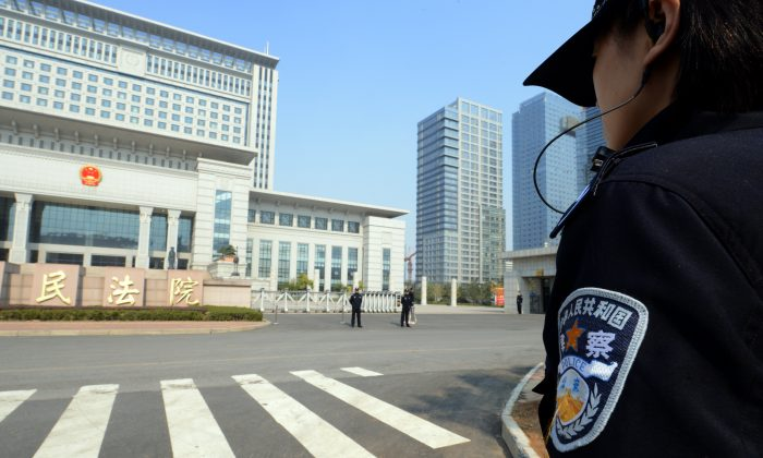 Chinese police guard the Shandong high court building in Jinan, east China Shandong province on October 25, 2013.