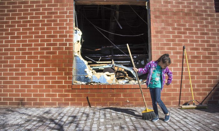 A young girl sweeps up the area outside the CVS Pharmacy in Baltimore that was set on fire during rioting on Monday, on April 28, 2015. (JIM WATSON/AFP/Getty Images)
