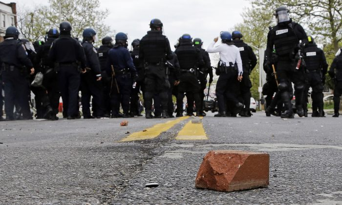 A brick sits on a street as police standby, Monday, April 27, 2015, during a skirmish with demonstrators after the funeral of Freddie Gray in Baltimore. Gray died from spinal injuries about a week after he was arrested and transported in a Baltimore Police Department van. (AP/Patrick Semansky)