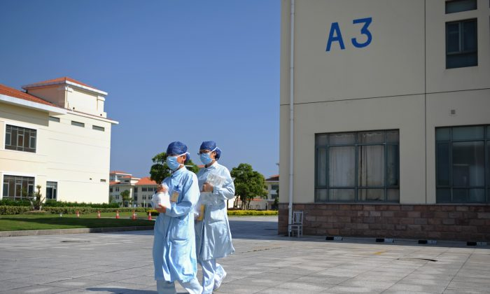 In this photo taken on May 14, 2013 two nurses walk at an isolation hospital in southwest Shanghai. (Peter Parks/AFP/Getty Images)