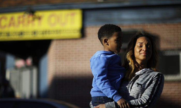 Cierra Powell and her son, Keon Lovitt, 6, at an outdoor church service a block from Monday's riots after the funeral for Freddie Gray, who died in police custody, in Baltimore on April 28, 2015. (AP Photo/David Goldman)