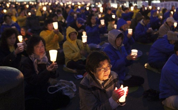 Falun Dafa practitioners hold a candlelight vigil as a peaceful protest near the Chinese Consulate in New York, on April 25, 2014. Falun Gong practitioners have peacefully exposed the persecution of their beliefs in China. (Samira Bouaou/Epoch Times)