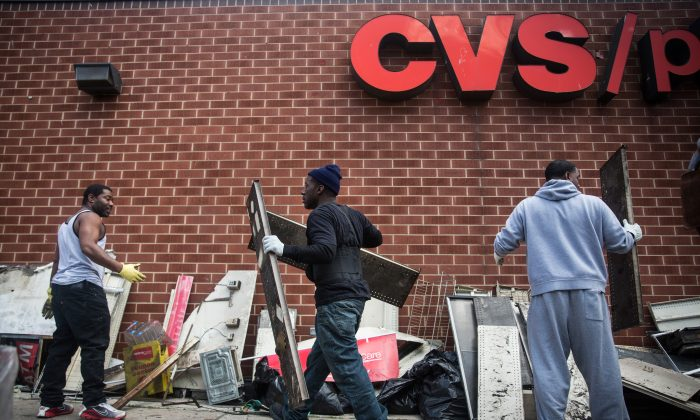Volunteers help clean up debris on April 28 from the CVS pharmacy that was set on fire during the rioting in Baltimore. (Andrew Burton/Getty Images)