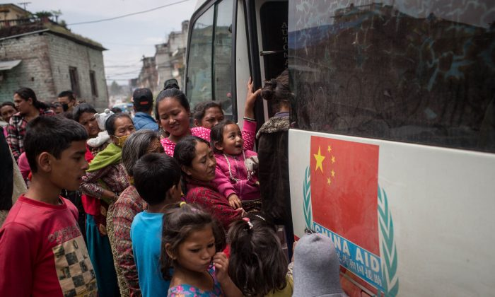 People wait in line to be seen by doctors at a mobile hospital bus on April 30, 2015 in Kathmandu, Nepal. (Chris McGrath/Getty Images)
