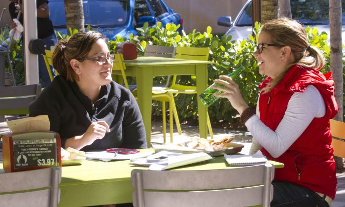 In this Tuesday, Jan. 27, 2015 photo, Sasha Rodriguez, left, and Adriana Olivieri dine on the patio at the BurgerFi restaurant in Aventura, Fla. Companies such as the gourmet hamburger chain BurgerFi plan to nearly double in size from their existing 65 restaurants this year. (AP Photo/Wilfredo Lee)