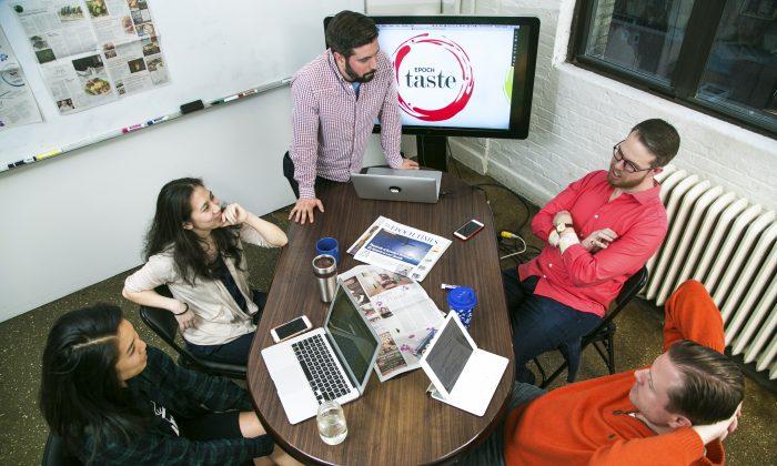 The Epoch Taste team discuss the new logo for Epoch Taste. (Benjamin Chasteen/Epoch Times)