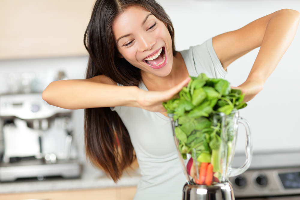 woman making green smoothies with blender home in kitchen