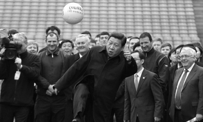 Then Chinese deputy leader Xi Jinping (C) kicks a Gaelic football as he visits at Croke Park in Dublin, Ireland on February 19, 2012. (Peter Muhly/AFP/Getty Images)