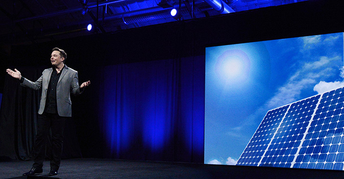 Elon Musk, CEO of Tesla, with a graphic unveils suite of batteries for homes, businesses, and utilities at the Tesla Design Studio April 30, 2015 in Hawthorne, California. (Kevork Djansezian/Getty Images)