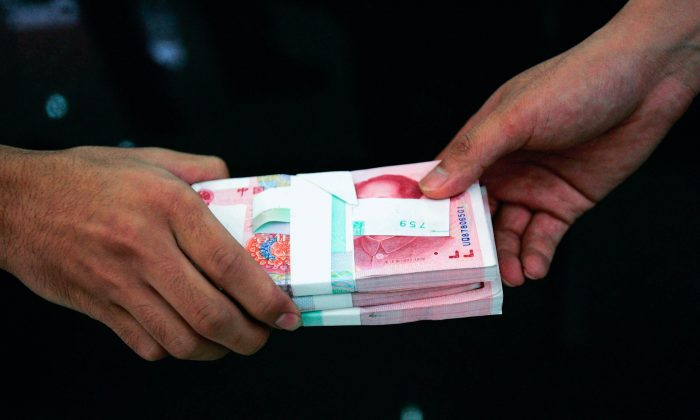 A clerk passes on stacks of Chinese yuan to another clerk at a bank on July 22, 2005 in Beijing, China.