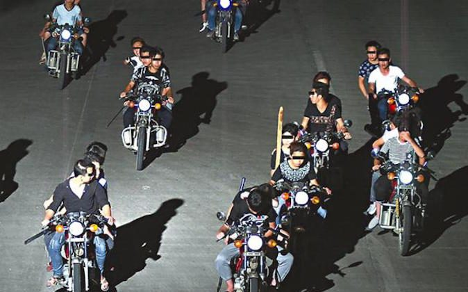 Knife-wielding bikers on the move in an undated photo. (Screen shot/Apple Daily)
