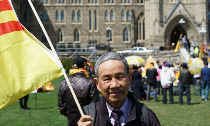 Mien Nguyen holds a flag at the Journey to Freedom Day rally on Parliament Hill, April 30, 2015. Nguyen and his family walked through Cambodia to Thailand to escape from Vietnam before they eventually made it to Canada. (Pam McLennan/Epoch Times)