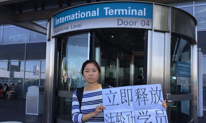 Zhao Guixin, the daughter of detained Falun Gong practitioner Zhao Guoliang, holds a sign asking for the release of Falun Gong practitioners outside San Francisco International Airport on April 23, 2015. (Provided by Zhao Guixin)