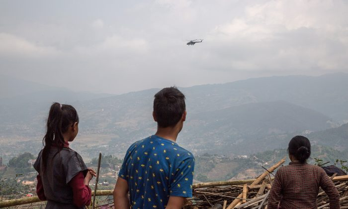 Residents look at a helicopter delivering aid in remote areas of quake-struck Nepal on May 1, 2015 in Kalchowk, Nepal. (Omar Havana/Getty Images)