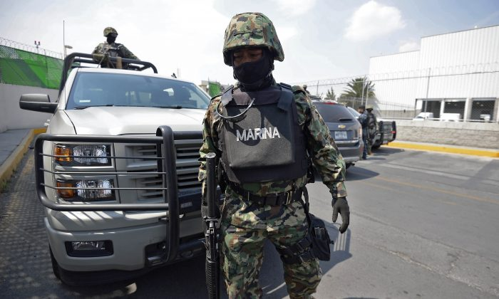 """Members of the Mexican Navy stand guard during an operation to present Mexican drug trafficker Joaquin Guzman Loera aka """"el Chapo Guzman"""" to the press, on February 22, 2014 in Mexico City.  (Alfredo Estrella/AFP/Getty Images)"""