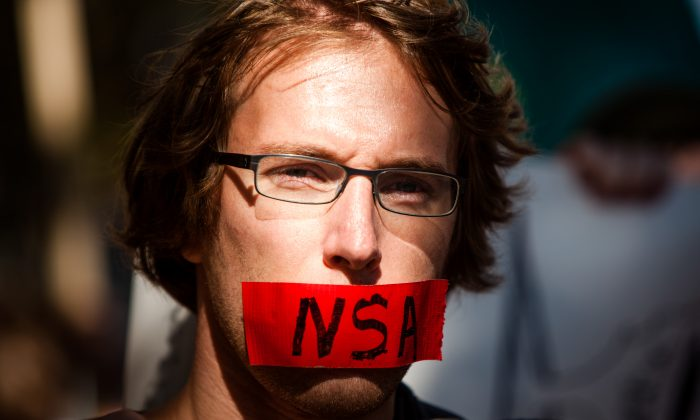 A protester with a piece of tape covering his mouth during the Stop Watching Us Rally protesting surveillance by the NSA, in Washington on Oct. 29, 2013. (Allison Shelley/Getty Images)