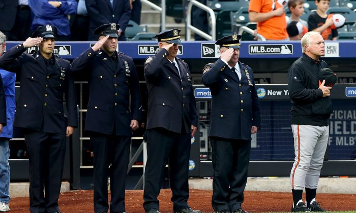Manager Buck Showalter (R) of the Baltimore Orioles and members of the NYPD salute as the national anthem is played before the game between the New York Mets and the Baltimore Orioles at Citi Field in Queens, New York City, on May 5. The New York Mets had a moment of silence in honor of slain Queens officer Brian Moore. (Elsa/Getty Images)