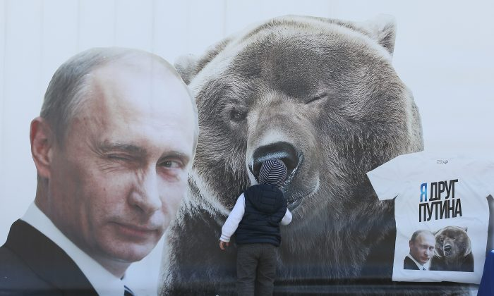 A boy inspects a billboard showing a winking Russian President Vladimir Putin and a bear at Victory Park on May 8, 2015 in Moscow, Russia. Chinese leader Xi is heading to Russia for events celebrating the 70th anniversary of the victory over Nazi Germany and the end of World War II. (Sean Gallup/Getty Images)