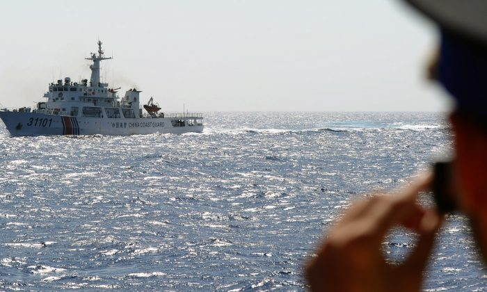 A Vietnamese coast guard officer takes a picture of a China Coast Guard ship in the South China Sea on May 14, 2014, off Vietnam's central coast. The Chinese regime is now defending airspace over the region. (Hoang Dinh Nam/AFP/Getty Images)